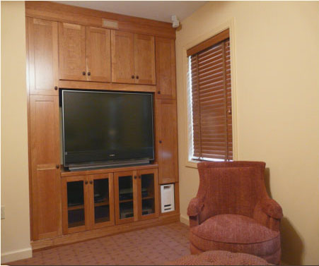 The guest chair swivels for TV viewing; note the wall of storage for the couple as well as guests.