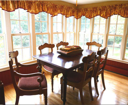 Dining area in New England farmhouse features beautiful reproduction period furniture. Note how the window topper shape plays off of the chair backs.