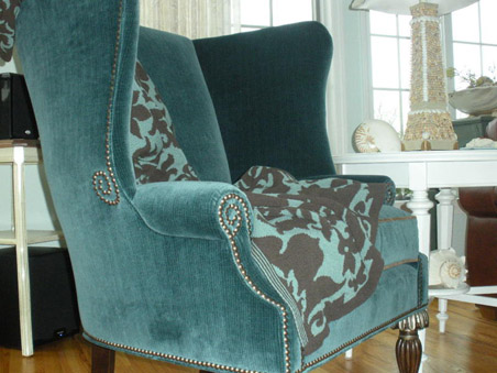 This fireside chair in teal velvet with its sinuous pewter nail head and metal-capped carved wood legs puts the 'wow' in 'wing'.