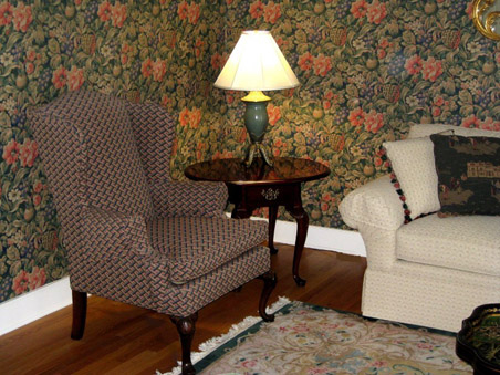 A densely patterned wallcovering sets the color palette and a cozy feel for the living room.