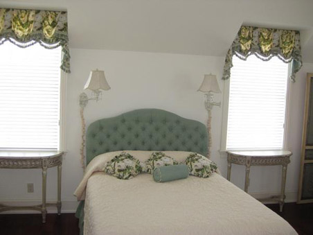 Beautiful formal balance frames the queen sized bed.
